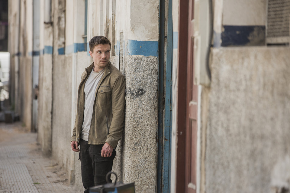 Joe Dempsie jako Harry Clake w szpiegowskim serialu stacji FOX DEEP STATE. Prawa autorskie: FOX Networks Group.<br><br>