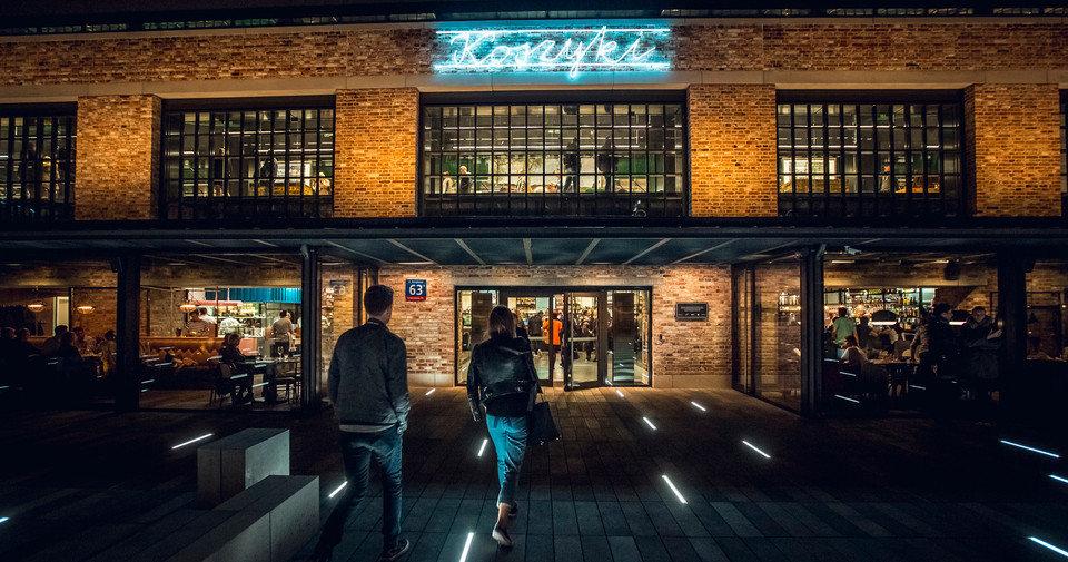 Widok od frontu na Halę Koszyki z charakterystycznym neonem nad wejściem.