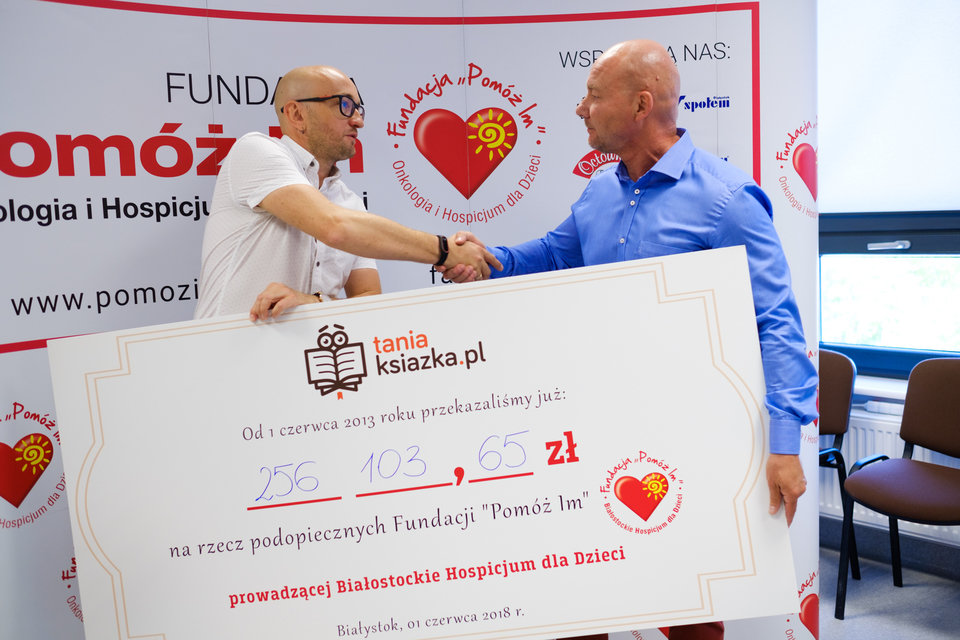 Łukasz Kierus, właściciel księgarni TaniaKsiazka.pl (z lewej) wręcza symboliczny czek Arnoldowi Sobolewskiemu, prezesowi Fundacji